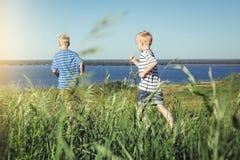 Dos muchachos en las camisetas rayadas que corren hacia fuera Imagenes de archivo