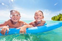 Dos muchachos en matrass inflables en el mar Imagen de archivo libre de regalías