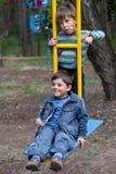 Dos muchachos en un oscilación Fotografía de archivo libre de regalías