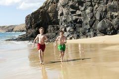 Dos muchachos están corriendo a lo largo de la playa Foto de archivo libre de regalías