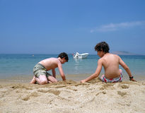 Dos muchachos están jugando en la playa Foto de archivo
