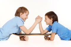 Dos muchachos están luchando en un patín Fotografía de archivo