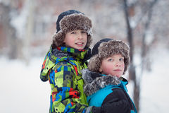 Dos muchachos felices alegres que juegan en parque del invierno Imagen de archivo libre de regalías