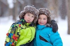 Dos muchachos felices alegres que juegan en parque del invierno Fotos de archivo