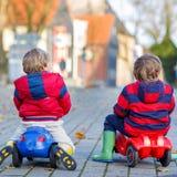 Dos muchachos felices de los amigos que juegan con el coche colorido del juguete, al aire libre Imágenes de archivo libres de regalías