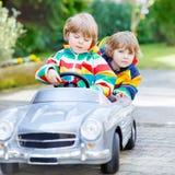 Dos muchachos felices del hermano que juegan con el coche viejo grande del juguete Imagenes de archivo