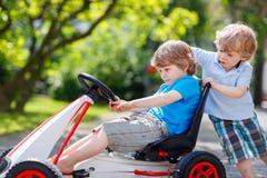 Dos muchachos felices del hermano que se divierten con el coche del juguete Imágenes de archivo libres de regalías