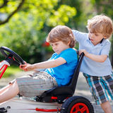 Dos muchachos felices del hermano que se divierten con el coche del juguete Fotografía de archivo libre de regalías