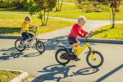 Dos muchachos felices que completan un ciclo en el parque imágenes de archivo libres de regalías