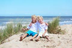 Dos muchachos felices que juegan en dunas en la playa Foto de archivo