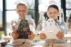 Dos muchachos felices que muestran a sus guerreros cósmicos robóticos Fotos de archivo