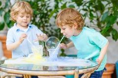 Dos muchachos gemelos que hacen el experimento con las burbujas coloridas Imágenes de archivo libres de regalías