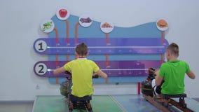 Dos muchachos hacen ejercicio del deporte en el aparato del entrenamiento en museo de la ciencia popular metrajes