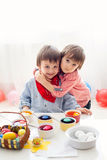 Dos muchachos, huevos que colorean para Pascua en casa foto de archivo libre de regalías