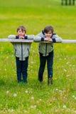 Dos muchachos inclinados en una cerca Imágenes de archivo libres de regalías