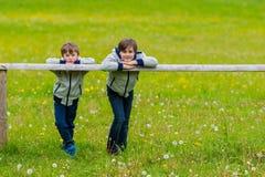 Dos muchachos inclinados en una cerca Imagen de archivo libre de regalías