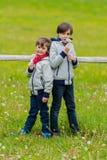 Dos muchachos inclinados en una cerca Foto de archivo libre de regalías