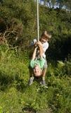 Dos muchachos jovenes en el oscilación de la cuerda Fotografía de archivo libre de regalías