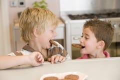 Dos muchachos jovenes en la sonrisa de las galletas de la consumición de la cocina Imagenes de archivo