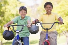 Dos muchachos jovenes en las bicicletas al aire libre que sonríen Imagen de archivo libre de regalías