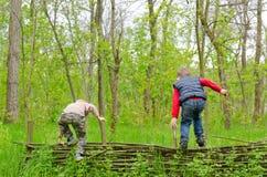Dos muchachos jovenes que juegan en una cerca rústica Imagen de archivo libre de regalías