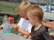 Dos muchachos jovenes que se sientan en una tabla con una botella de Gatorade Foto de archivo