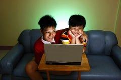 Dos muchachos jovenes que usan un ordenador portátil y una sonrisa Foto de archivo libre de regalías