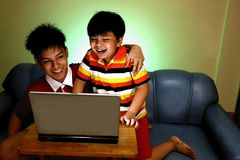 Dos muchachos jovenes que usan un ordenador portátil y una sonrisa Fotos de archivo libres de regalías