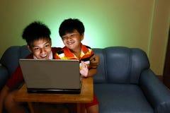 Dos muchachos jovenes que usan un ordenador portátil y una sonrisa Imágenes de archivo libres de regalías
