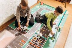 Dos muchachos juegan con los robots que crearon del constructor robótico en la bandera colorida en el piso en imagen de archivo libre de regalías
