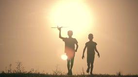Dos muchachos juegan con un avión de madera en la puesta del sol Silueta de los niños que juegan con el aeroplano Sueños del vuel metrajes