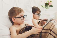 Dos muchachos juegan en el ordenador portátil y la tableta con el perro en cama Fotos de archivo libres de regalías