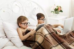 Dos muchachos juegan en el ordenador portátil y la tableta con el perro en cama Fotografía de archivo libre de regalías