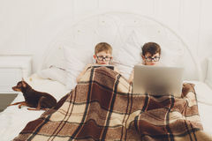 Dos muchachos juegan en el ordenador portátil y la tableta con el perro en cama Imagen de archivo