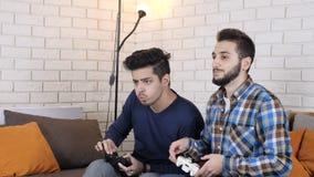 Dos muchachos juegan a un juego de la consola, uno de ellos los triunfos 50 fps
