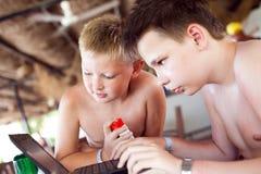 Dos muchachos juegan una computadora portátil en resto en una barra en una playa Foto de archivo libre de regalías
