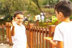 Dos muchachos juegan y soplan burbujas de jabón en el parque de Kugulu foto de archivo