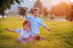 Dos muchachos, jugando con el aeroplano en puesta del sol en el parque Imagen de archivo