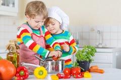 Dos muchachos lindos del niño que cocinan la sopa y la comida italianas con los fres Foto de archivo libre de regalías