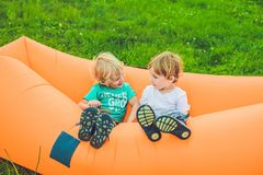 Dos muchachos lindos que descansan sobre un sofá del aire en el parque Fotos de archivo libres de regalías