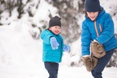Dos muchachos lindos que juegan afuera en naturaleza del invierno fotos de archivo