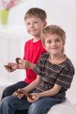 Dos muchachos lindos que se sientan en el sofá Imágenes de archivo libres de regalías