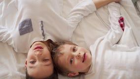 Dos muchachos mienten en la cama, hablando y mirando el techo almacen de video