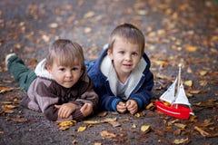 Dos muchachos, mintiendo en la tierra, jugando con un barco Foto de archivo