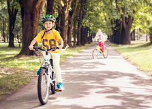 Dos muchachos montan una bicicleta en parque Foto de archivo libre de regalías
