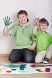 Dos muchachos muestran las palmas derechas manchadas con las pinturas Fotografía de archivo