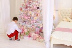 Dos muchachos prepararon los regalos del ` s del Año Nuevo debajo del árbol de navidad del Imagen de archivo libre de regalías