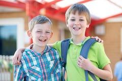 Dos muchachos que colocan la escuela exterior con las bolsas de libros Fotos de archivo libres de regalías