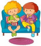 Dos muchachos que comen el bocado y que beben soda en el sofá Imágenes de archivo libres de regalías