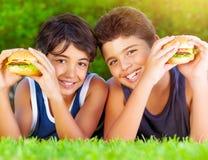 Dos muchachos que comen las hamburguesas Fotos de archivo libres de regalías